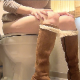 A redhead girl takes a piss and a shit while sitting on a toilet while wearing long suede boots. A crackling shit is heard, but no product is shown. Over 4 minutes.